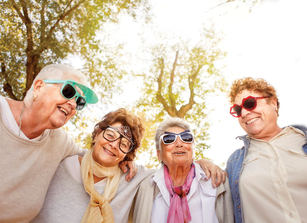 Four older women pose closely together outdoors while wearing funny sunglasses