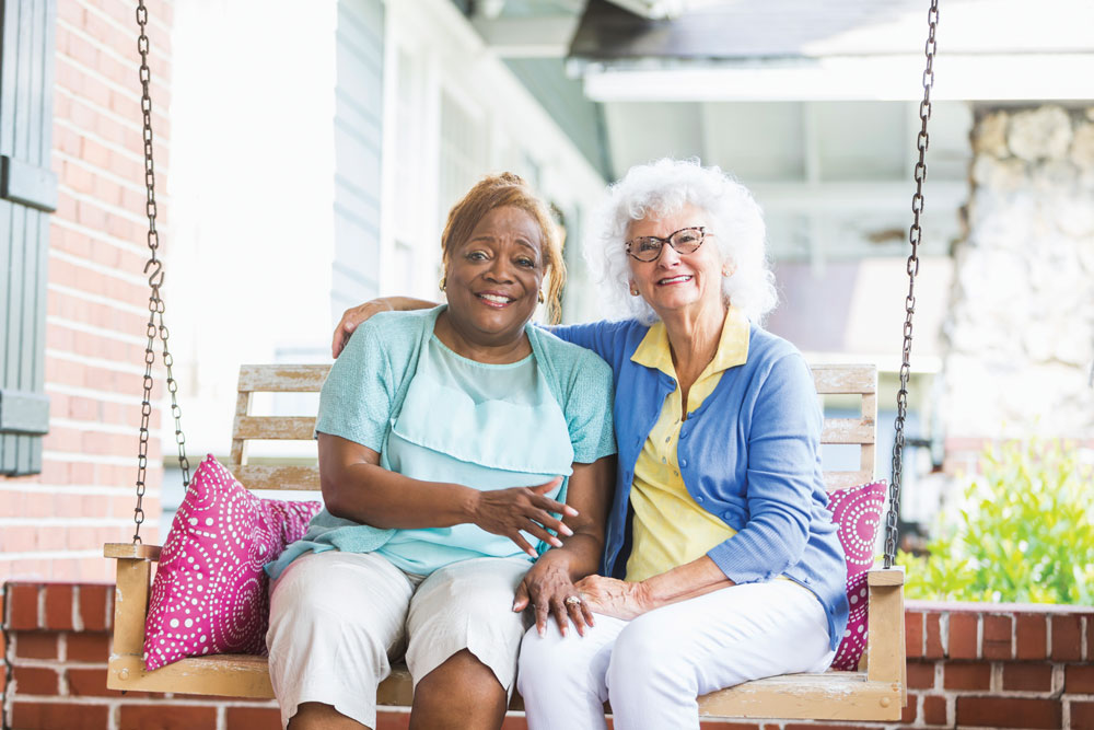 Two female Charter Senior Living of Hermitage residents sit together and smile on an outdoor swing