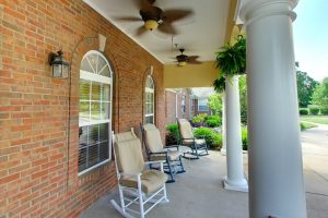 Porch with large white pillars, rocking chairs, ceiling fans, and hanging plants