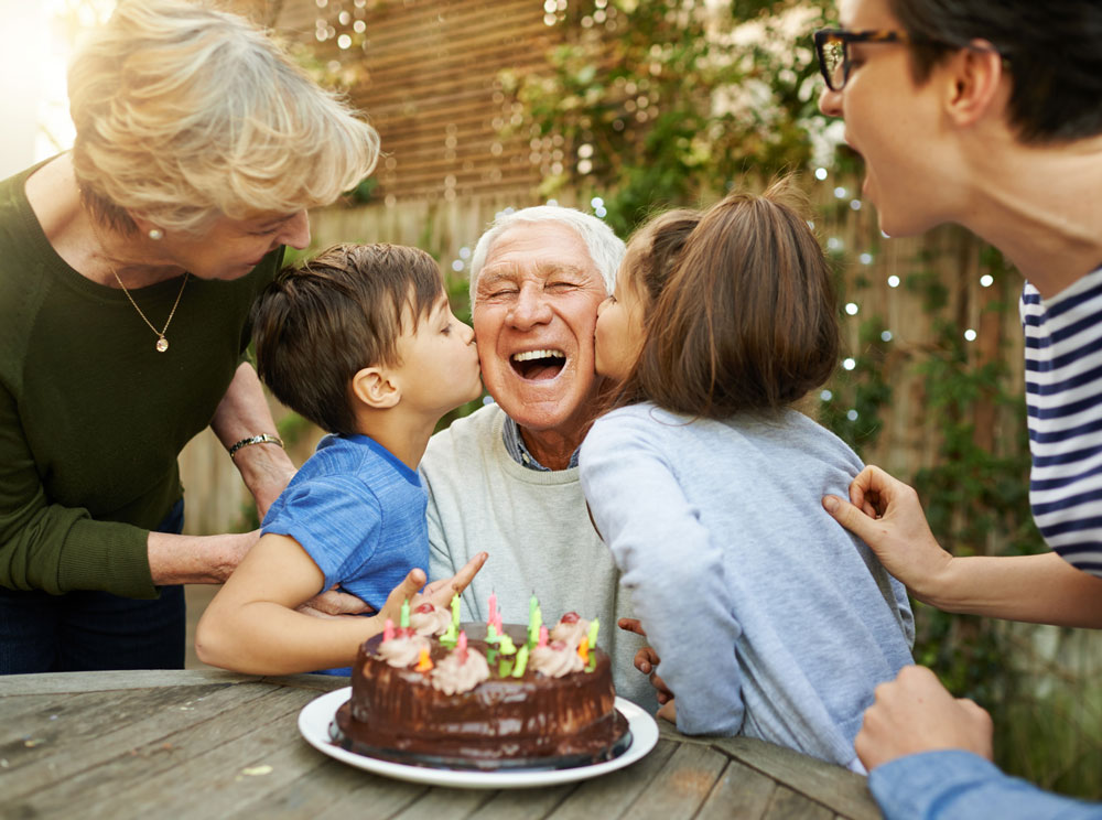 Older man celebrates his birthday outdoors with his family and a cake while receiving kisses on the cheek