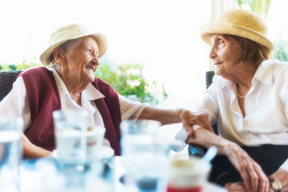 Two older women wearing hats sit next to each other at outdoor table and smile