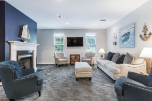 Nautical-themed sitting room with various seating options, blue accents, side tables, television, and carpeted floors