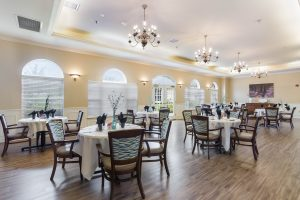 Large dining space with table and chair sets, centerpieces, windows, chandeliers, and hardwood floors