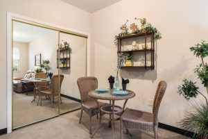 Dining area with table, two chairs, closet with sliding mirror doors, and several plants decorating the space